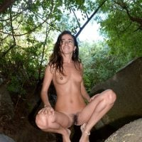 Slim Nudist Woman Squatting in the Woods