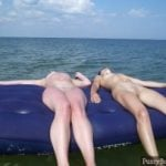 Two Nude Girls floating Relaxing on intlatable mattress on the ocean